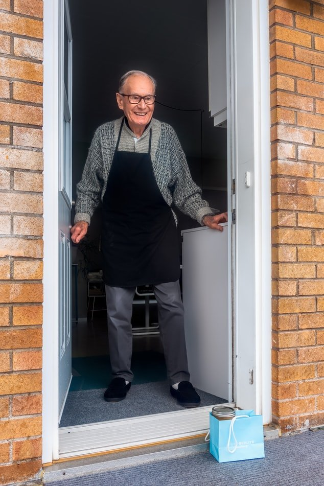 old person in front of house